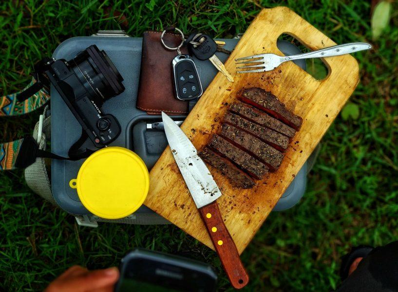 un kit de viaje, carne, cubiertos, camara de fotos, taper, etc